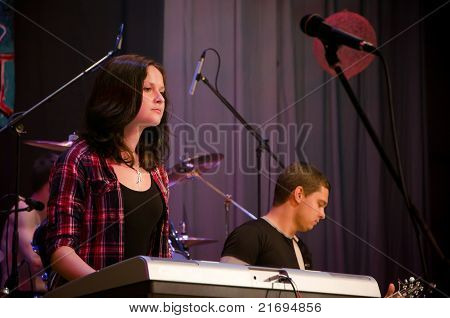 Girl playing on a keyboard on a concert in the spotlight.