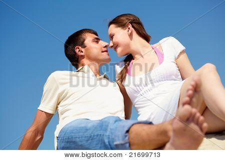 Photo of peaceful couple looking at each other with blue sky on background