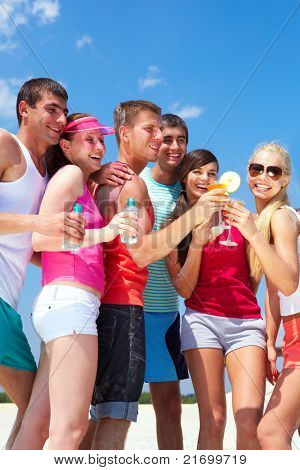 Portrait of happy young friends holding cocktails during beach party