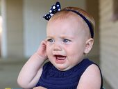 stock photo of teething baby  - pretty baby crying and holding her ear in pain - JPG