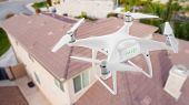 Unmanned Aircraft System (UAV) Quadcopter Drone In The Air Over House Inspecting the Roof. poster