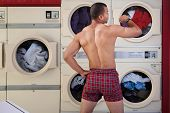 stock photo of partially clothed  - Muscular man in boxer shorts looks at wristwatch in laundromat - JPG