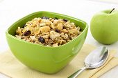 picture of cereal bowl  - delicious and healthy wholegrain muesli breakfast with lots of dry fruits nuts grains and a fresh apple - JPG