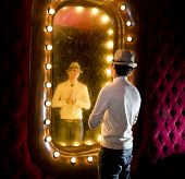 stock photo of peddlers  - retro young man looks at himself in mirror - JPG