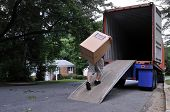 An unidentifiable person is carrying a heavy moving box up a ramp into the back of a moving truck (a
