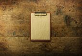 Old clipboard with blank old paper, on rustic and grungy wooden surface, with plenty of copy space. poster