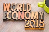 world economy 2018 -word abstract in vintage letterpress wood type with a cup of coffee poster