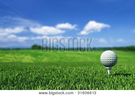 Golf Ball On Tee On The  Green Grass