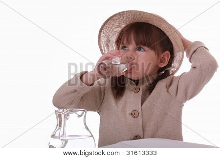 A Little Girl Sits And Drinks Water From A Glass