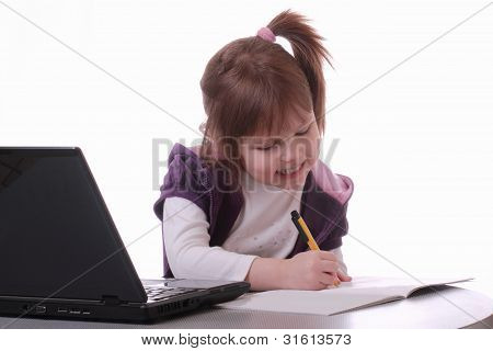A Little Girl Is Sitting Near The Laptop And Draws With A Pen