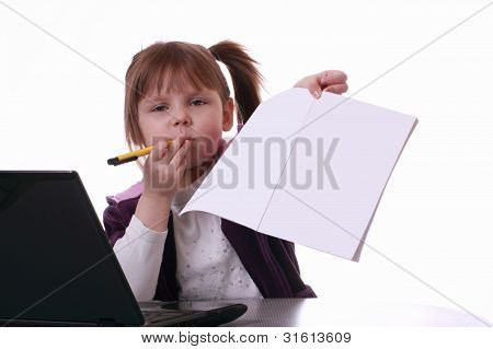 A Little Girl Is Sitting Near The Notebook And Shows The White Paper