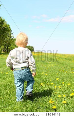 Criança andando em campo verde