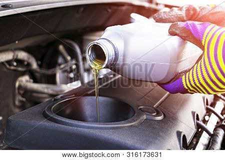 poster of Change The Oil. Hand Mechanic In Repairing Car. Close Up Oil For Car Engine. Motor Oil Pouring To Ca