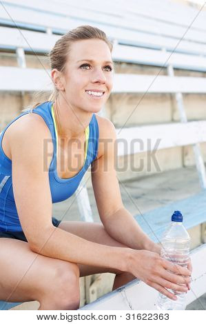 Athlete Sitting In Bleachers With Water Bottle
