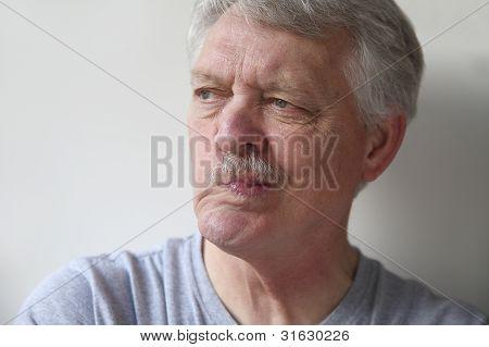 senior man distorts his mouth