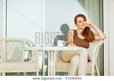 Thoughtful Woman Sitting On Terrace