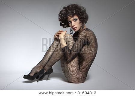 Sexy Glamor Girl With Curly Hair In Black Clothes, Sitting And Hugging Himself With His Hands Behind