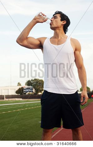 Young Male Latino Athlete Drinking Water