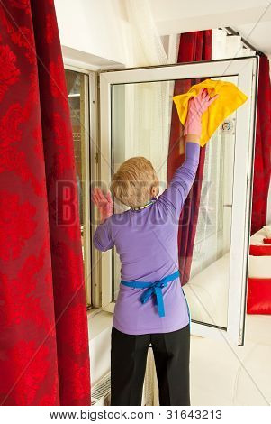 Rear View Of Woman Cleaning Window