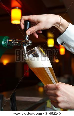 the bartender pours the beer
