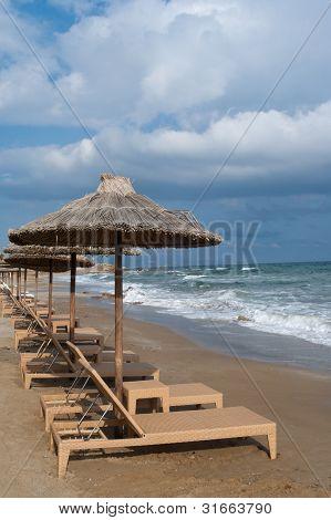 Empty Beach Chairs Under Umbrellas On Mediterranean Beach