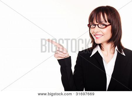 Smiling attractive young businesswoman pointing to her right towards blank copyspace