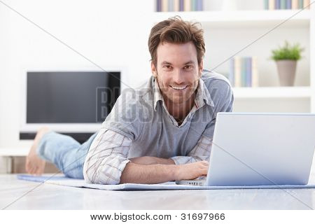 Casual young man laying on floor at home, browsing internet, smiling.