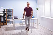 Handicapped Businessman Walking On Hardwood Floor With Crutches At Workplace poster