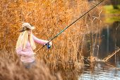 picture of fisherwomen  - beautiful blond girl in pink sweater fishing - JPG