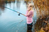 stock photo of fisherwomen  - beautiful blond girl in pink sweater fishing - JPG