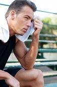 foto of bleachers  - Portrait of a young athletic man with workout towel sitting on the bleachers - JPG