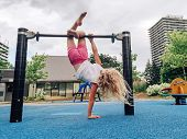 Cute Adorable Little Preschool Blonde Caucasian Girl Hanging Upside Down On Pullup Bar On Playground poster