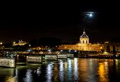 Institut De France And People Walking On Pont Des Arts At Night - Paris, France. poster