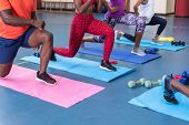 Low section of diverse fit people performing yoga together on a exercise mat in fitness center. Brig poster