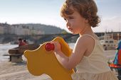 stock photo of lurch  - A playful little girl is rocking on the playground - JPG