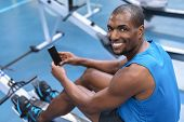Portrait of African-american fit man using mobile phone while exercising on rowing machine in fitnes poster