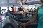Side view of diverse Fit women exercising on treadmill in fitness center. Bright modern gym with fi poster