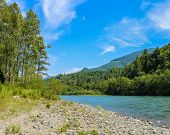 A Stunning View Of The Skagit River On A Beautiful Summer Day, With Cloud Trails And A Rocky Beach P poster