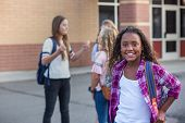 Cute, diverse pre-adolescent teen student hanging out with friends after school. Selective focus on  poster