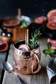 Blood Orange Cocktail In A Copper Mug With Red Orange And Lemon, Cinnamon And Mint On A Wooden Backg poster