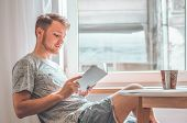 Attractive Young Man Is Reading A Book At Home. Thoughtful Guy Reading Important Book. Reading And D poster