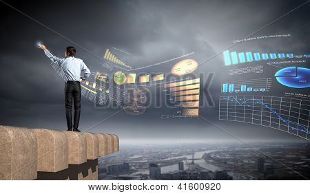 young businessman man standing with back drawing diagram against city background