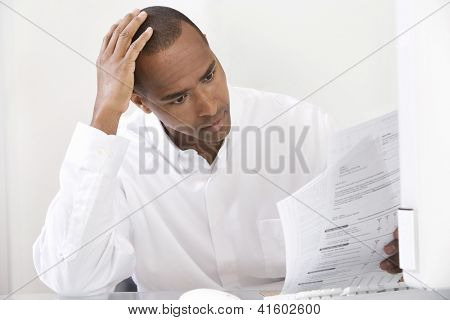 Tensed African American male executive with paperwork