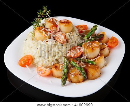 Risotto with pan seared sea scallops, cheese and vegetables  isolated on black background