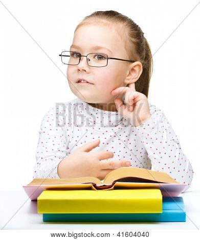 Cute little girl with books and glasses holding hand near her ear like listening to something, isolated over white