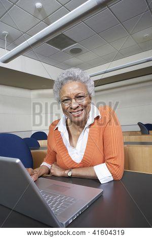 Senior teacher working on laptop in empty classroom