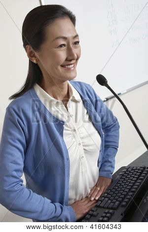 Happy mature teacher holding lecture