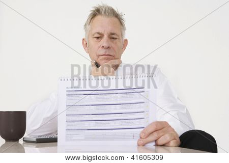 Senior businessman looking at investment brochure at office