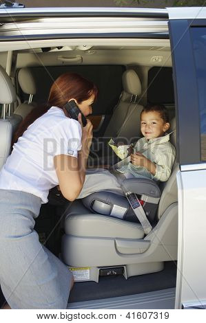 Business woman communicating on cell phone while looking at son sitting on baby car seat
