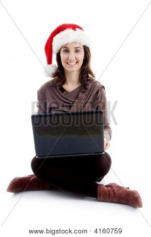 Cheerful Young Woman In Christmas Hat Posing With Laptop